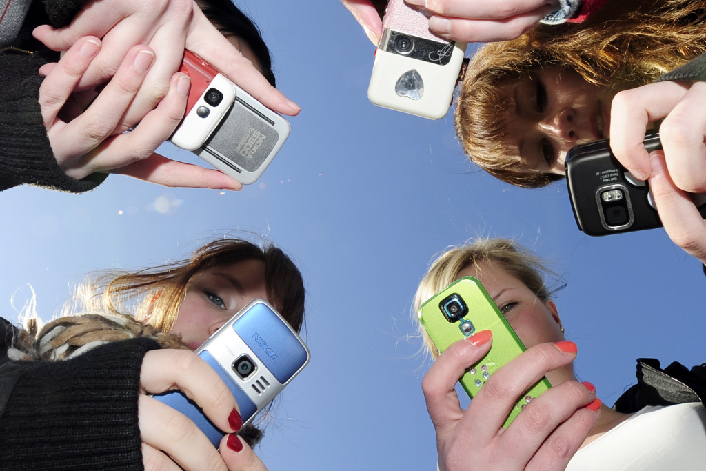 Teenagers use their mobile phones after school.