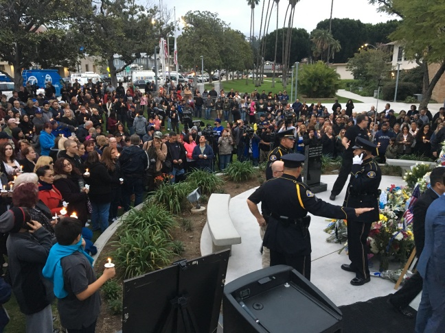 People gather in Whittier for a vigil for police officer Keith Boyer, who was shot and killed Monday morning after he and another officer tried to pat down a motorist involved in a traffic accident. The man was driving a stolen car officials say was connected to a murder hours earlier.