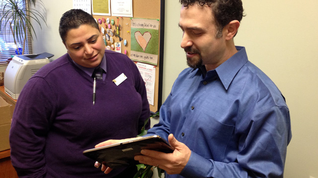 Priscilla Castillo, director of the Planned Parenthood clinic in Concord, and Jeff Novick, IT manager, look over a tablet.