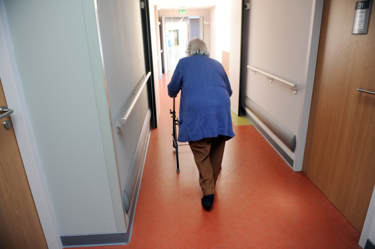 An elderly woman walks with a walker on
