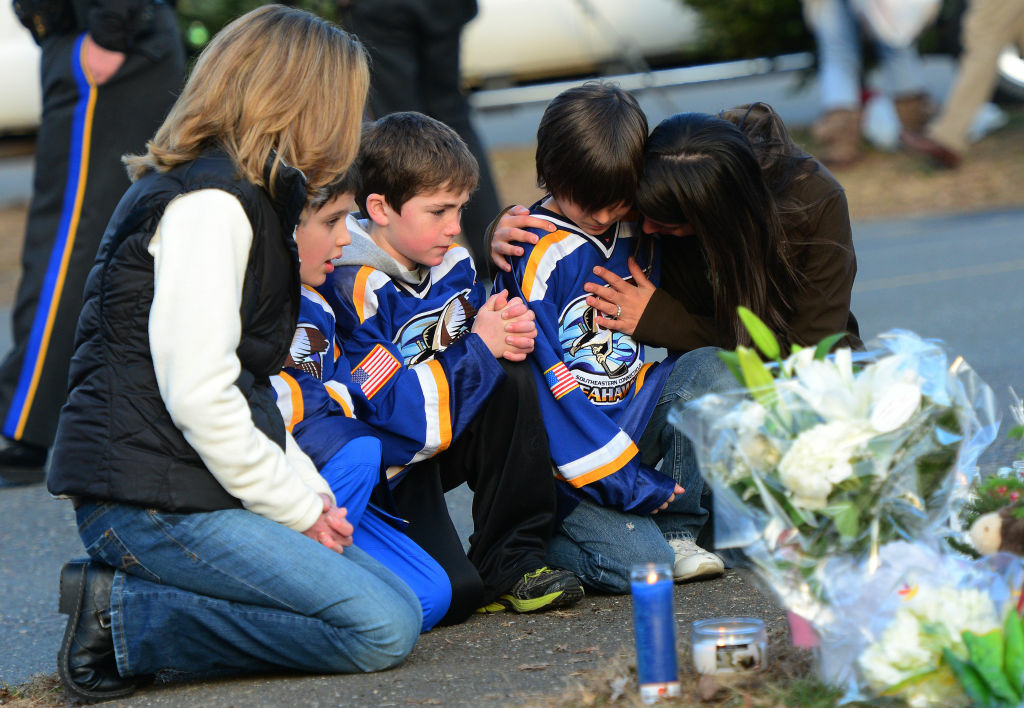 A family pays tribute to the victims of an elementary school shooting in Newtown, Connecticut, on December 15, 2012.
