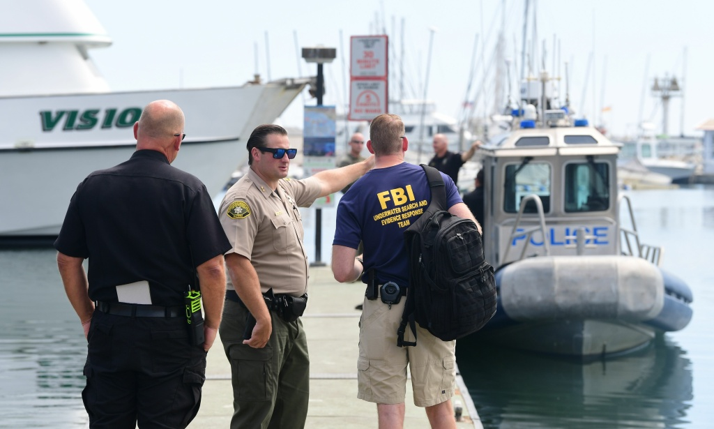 Law enforcement personnel, including a member of the FBI Underwater Search and Evidence Response Team wait on a jetty on September 3, 2019, in Santa Barbara, California.