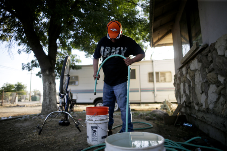 "FILLING BUCKETS; Looking for water to flush his toilet, Tino Lozano points a garden hose at some buckets on the bare dirt of his yard in Okieville, which is named for refugees from the 1930's Dust Bowl who came west from Oklahoma. But only a trickle comes out; then a drip, then nothing more. ""There it goes. That was all,"" he says. ""That's how we do it in Okieville now."""