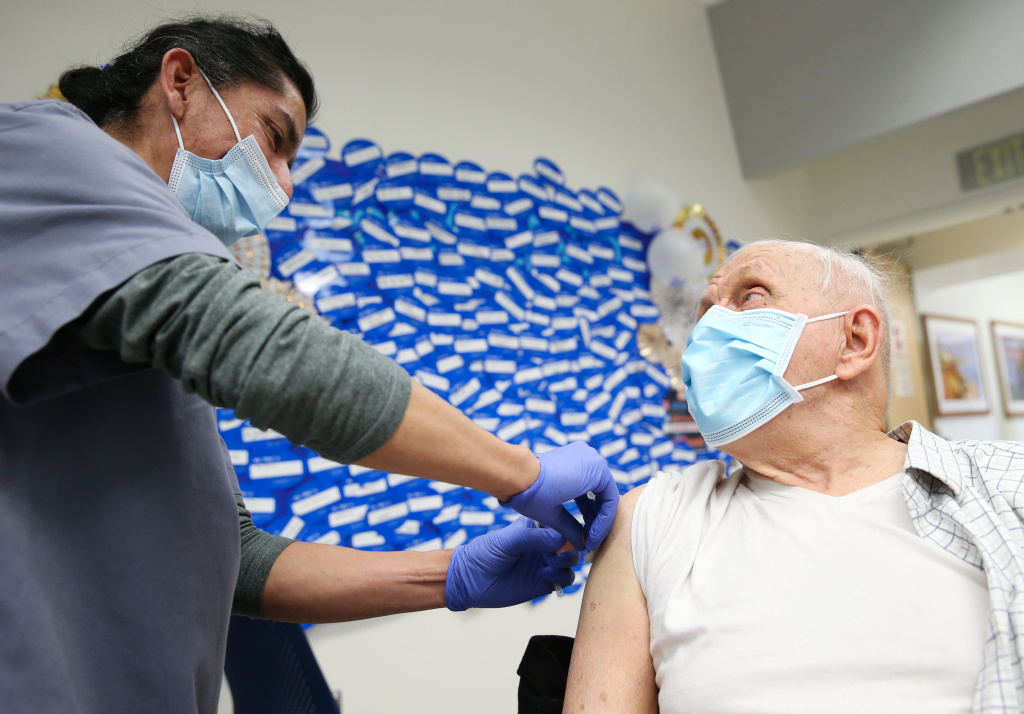 Certified medical assistant Mario Rivera applies a Band-Aid after administering a COVID-19 Pfizer vaccination to Anthony Banash at Harbor-UCLA Medical Center on January 21, 2021 in Torrance, California.