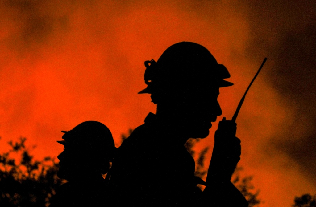 Firefighters watch the Blue Cut wildfire burning near the Cajon Pass, north of San Bernardino, California on August 16, 2016.