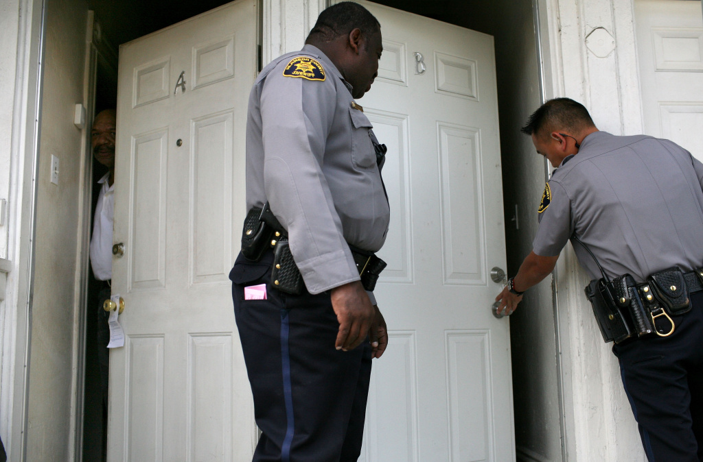 OAKLAND, CA - JUNE 04:  A neighbor peers out of his door as Alameda County Sheriff deputies Ken Cammack (C) and Ken Kong (R) enter an apartment to evict tenants who have defaulted on rent payments June 4, 2009 in Oakland, California. With high unemployment rates and a weak economy, many people are defaulting on rent and mortgage payments leaving the Alameda County Sheriff to enforce an increased number of evictions, as many as 500 a month, up significantly from one year ago.  (Photo by Justin Sullivan/Getty Images) *** Local Caption *** Ken Cammack;Ken Kong
