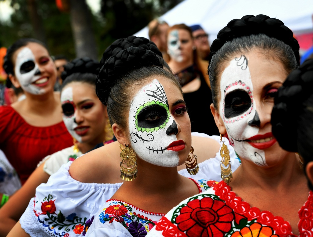 People in costume parade during the annual Dia de los Muertos (Day of the Dead) festival at the Hollywood Forever cemetery in Hollywood, California on October 29, 2016.