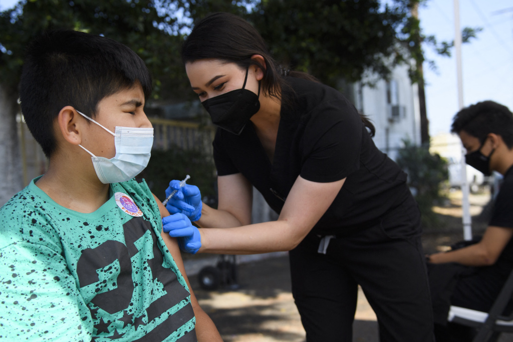 A 12-year-old child closes their eyes as they receive a first dose of the Pfizer Covid-19 vaccine at a mobile vaccination clinic at the Weingart East Los Angeles YMCA on May 14, 2021 in Los Angeles, California.