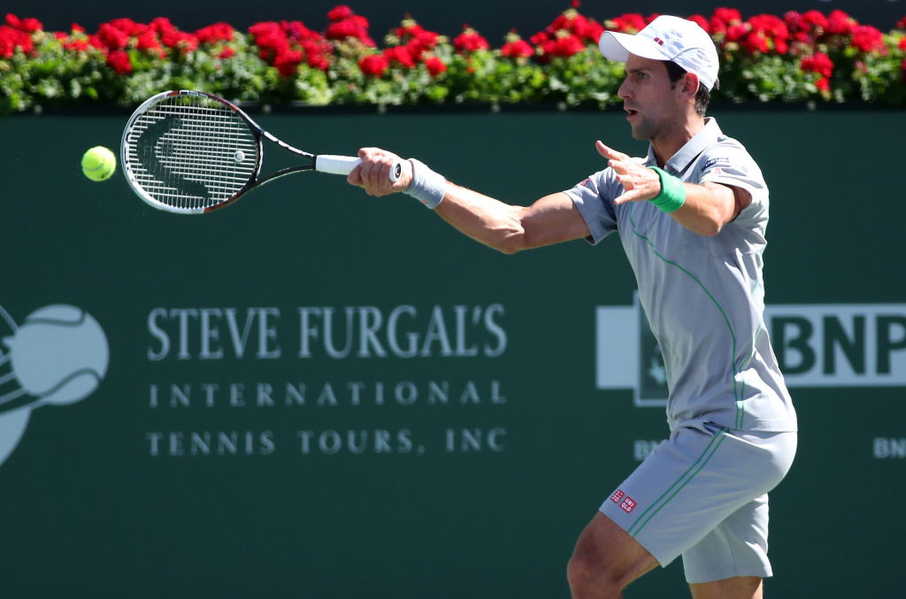 Novak Djokovic of Serbia hits a return to Roger Federer of Switzerland during the men's final of the BNP Paribas Open at Indian Wells Tennis Garden on March 15, 2014 in Indian Wells, California. Pennetta won 6-2, 6-1.