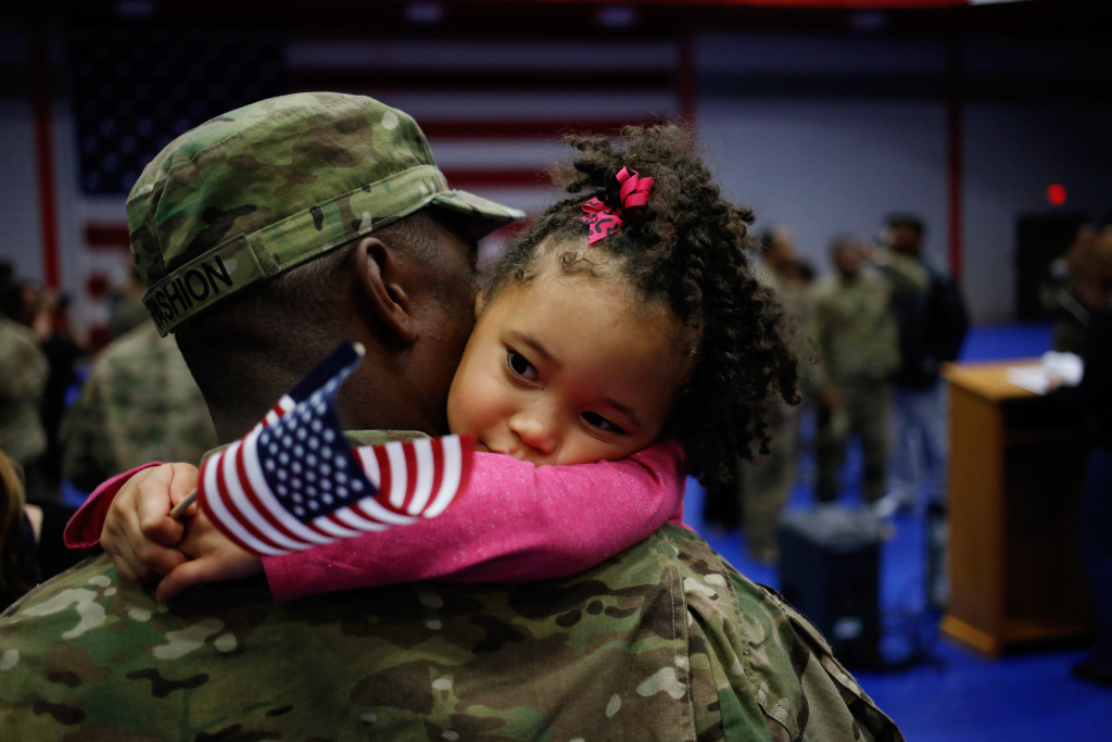 Spc. Michael Fashion of the U.S. Army's 3rd Brigade Combat Team, 1st Infantry Division, holds his daughter Malia Banks, 5, following a homecoming ceremony in the Natcher Physical Fitness Center on Fort Knox in the early morning hours of Wednesday, November 20, 2013 in Fort Knox, Ky.