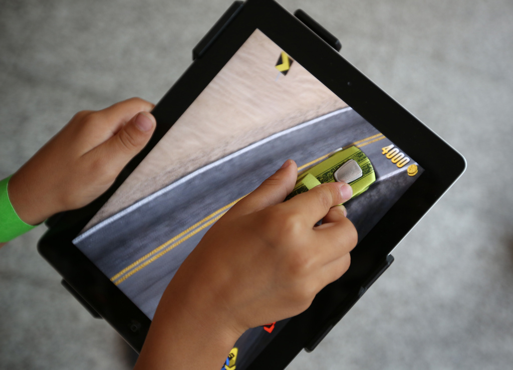A child plays with an iPad and the apptivity app at Westfield shopping Centre on August 21, 2012 in London, England.