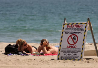 Nichole Canori (L) and Patrick Woodard sunbathe near a sign that warns beach-goers to stay out of the water, which was polluted by run-off from a nearby storm drain and creek, at Will Rogers State Beach on May 22, 2009 in Pacific Palisades, California.