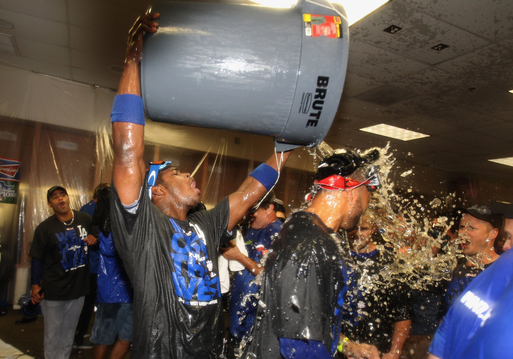 Yasiel Puig #66 of the Los Angeles Dodgers pours a bucket of liquids over Matt Kemp #27 as they celebrate in the locker room after defeating the Arizona Diamondbacks to clinch the National League West title and a postseason berth at Chase Field on September 19, 2013 in Phoenix, Arizona.