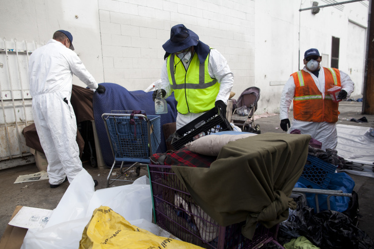 Workers clear garbage from San Julian Street in Skid Row as part of the Operation Healthy Streets program. The City of L.A.'s Bureau of Sanitation will remove three tons of trash from the streets, a spokesperson said.
