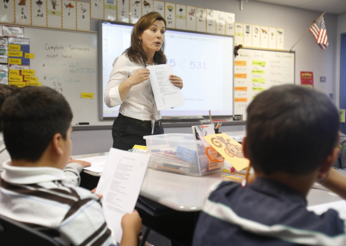 Second-grade teacher Vickie Boudouris goes over a worksheet in an English-learner summer school class at the Cordova Villa Elementary School in June, in Rancho Cordova, Calif. Under Gov. Jerry Brown's proposed budget, California schools will receive an ad
