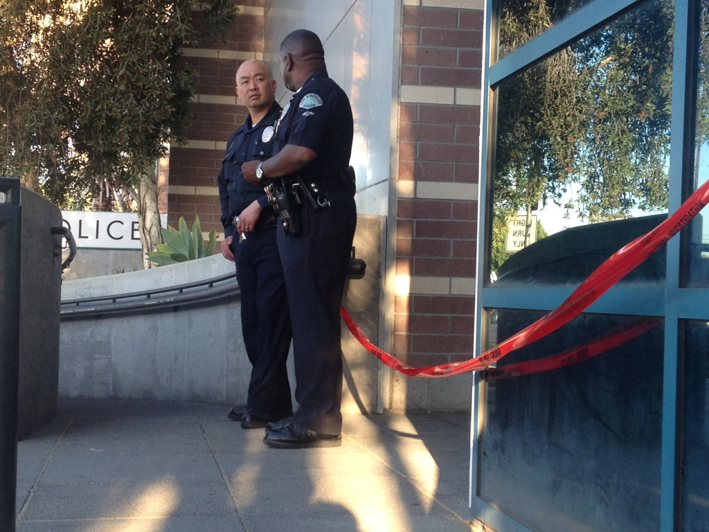 Police officers stand outside the Wilshire station on Tuesday, April 8, 2014. A gunman entered the lobby the night before and opened fire, striking one police officer before he was hit by return fire.