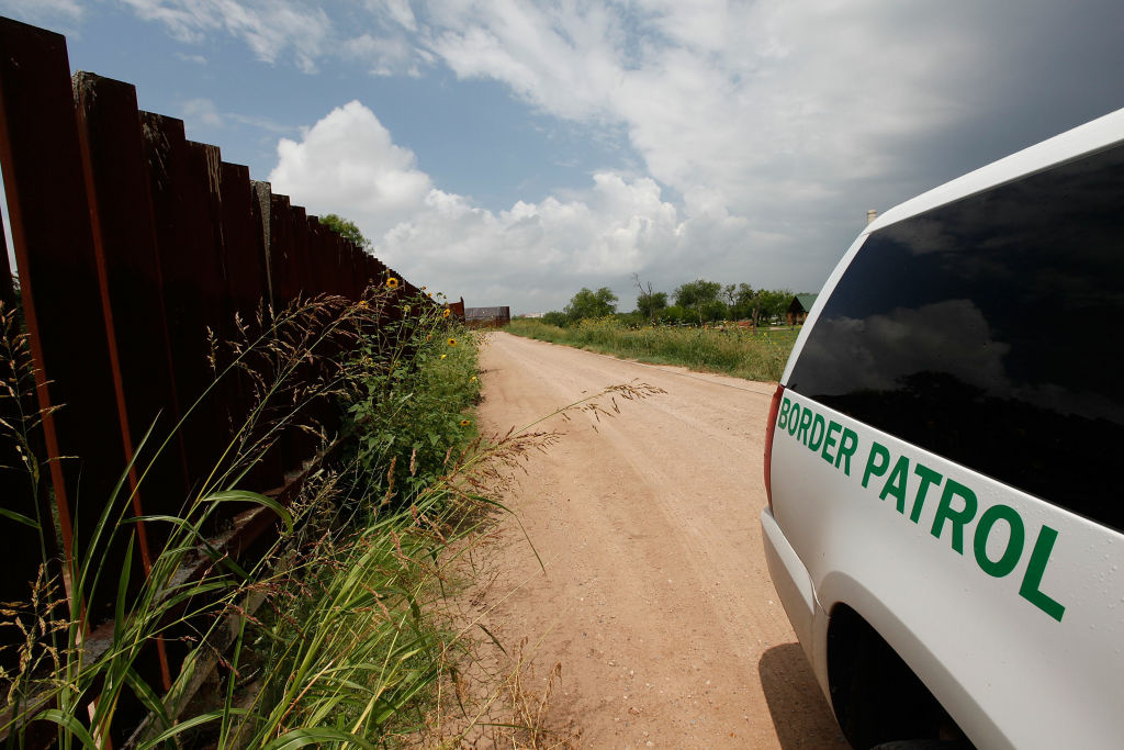 Parked next to a section of the border fence, a Border Patrol agent watches an area of the U.S.-Mexico border along the Rio Grande River near, Hidalgo, Texas.