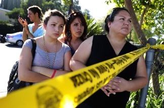 Family members wait for their children outside Gardena High School on Jan. 18, 2011 where two students were shot after a gun in another student's backpack accidentally discharged. From left to right are Eliut Maururi, Elisabeth Guerrero and Maria Avila.