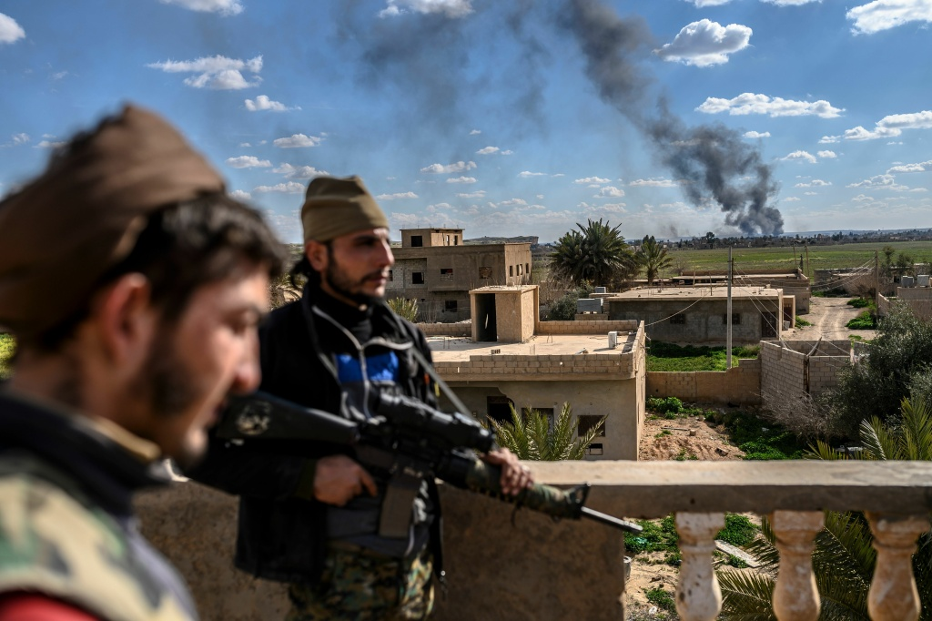U.S.-backed fighters stand guard on a building during shelling of the Islamic State's last holdout in the town of Baghouz, Syria, on March 3.