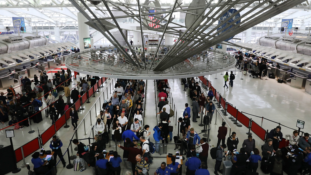 Travelers wait in the security line at John F. Kennedy International Airport in New York. On Wednesday, the Department of Homeland Security warned the state that it was freezing residents' access to Global Entry and similar programs, citing a recent state law that allows undocumented immigrants to obtain licenses.