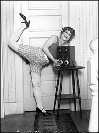 She just can't wait to hear this week's Dinner Party Download! According to the LAPL archive, she's 'a young woman almost dancing as she holds her radio and listens through earphones.'