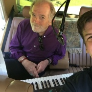 """Tom Petty and the Heartbreakers keyboardist Benmont Tench III lumbers into the back of John's car to record his song """"Like the Sun (Michoacan)""""."""
