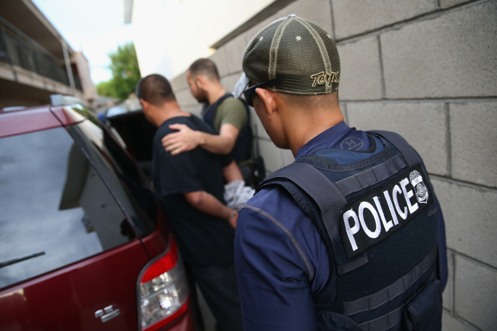 FILE PHOTO: A man is detained by U.S. Immigration and Customs Enforcement agents on Oct. 14, 2015 in Los Angeles, California. The agency says its arrests of immigrants went up by 38 percent during President Trump's first 100 days in office.