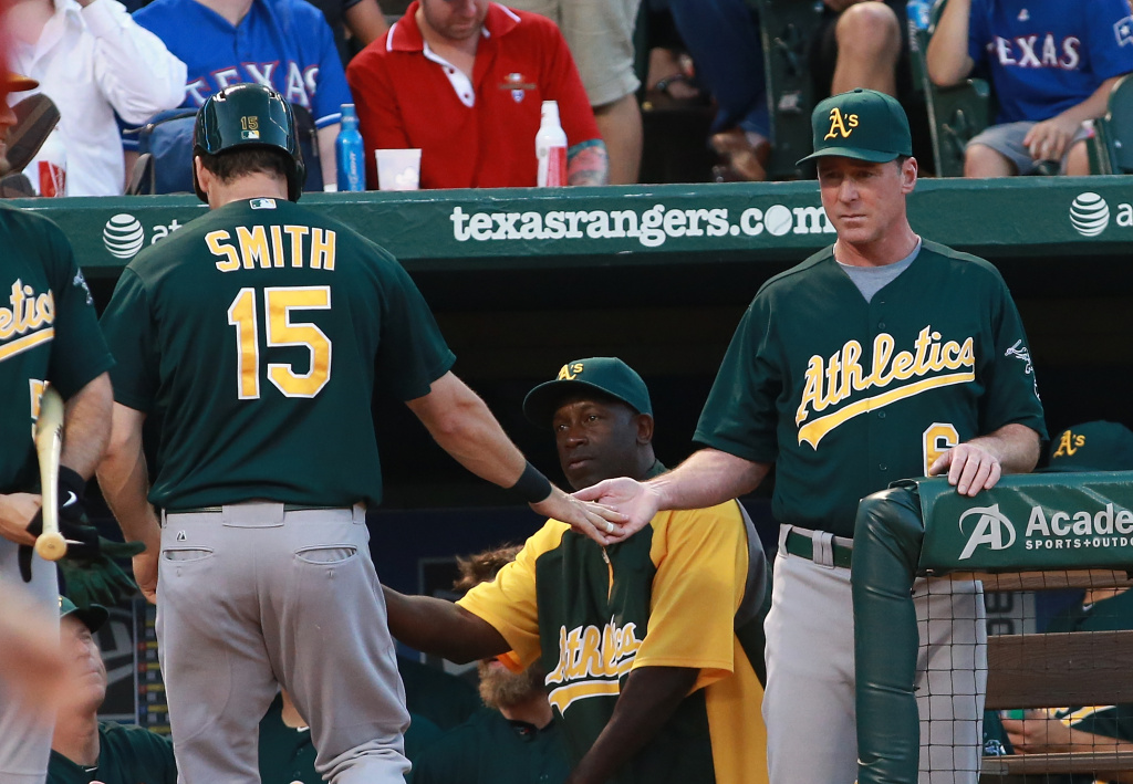 Seth Smith #15 of the Oakland Athletics is congratulated by Bob Melvin #6 of the Oakland Athletics for scoring in the fourth inning against the Texas Rangers at Rangers Ballpark in Arlington on June 18, 2013 in Arlington, Texas.