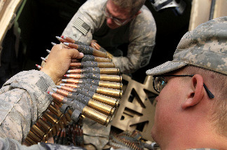 U.S. Army Specialist Craig Cox from Ogden, Utah (R) hands rounds of .50 caliber ammunition to U.S. Army Corporal Zachary Taylor with Task Force Thor Route Clearance Patrol from 23rd Engineering Company, Airborne as they prepare for a day-long route clearance mission July 7, 2010 in Jeluwar, Afghanistan.