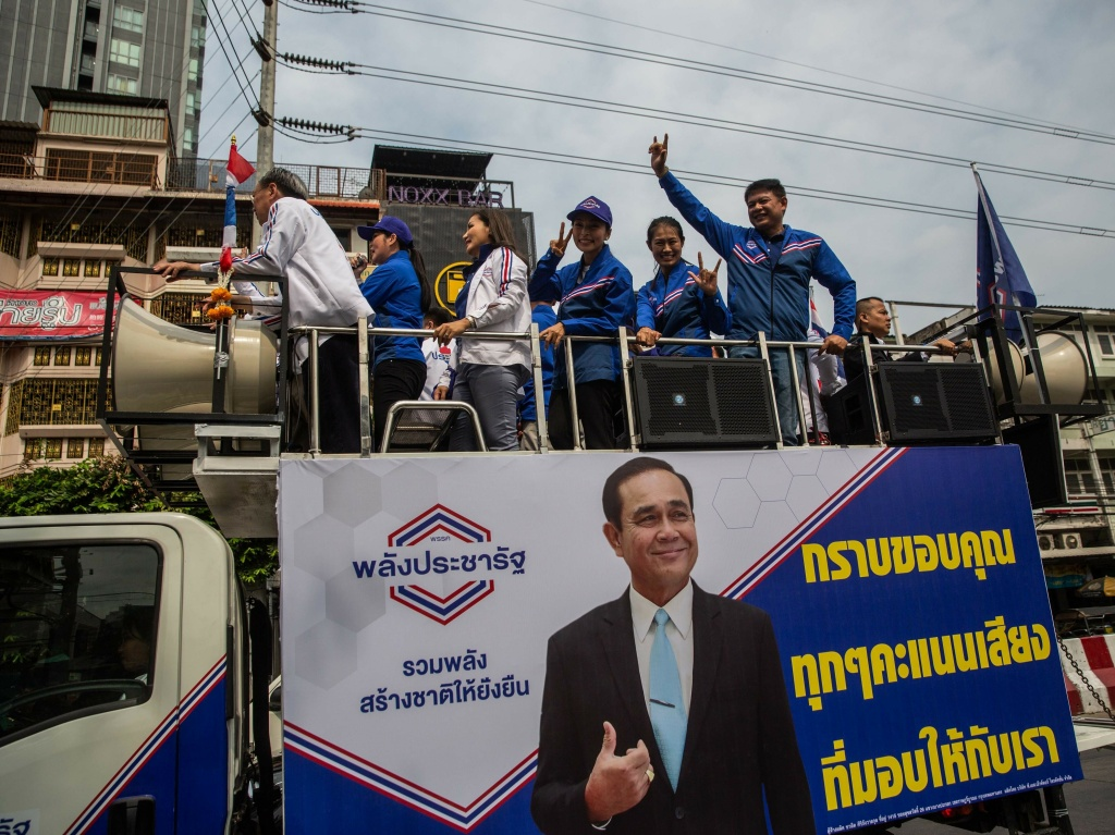 Members of Thailand's Palang Pracharath Party wave from a truck featuring posters of Prime Minister Prayuth Chan-o-cha, in Bangkok on Wednesday. The party took the lead in Thailand's first election since the army took power five years ago after a preliminary count by the election commission.
