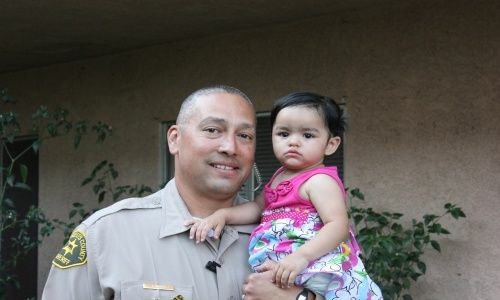 Deputy Joe Chavez with the 15-month-old La Puente girl whose life he saved at Bonelli Park on May 27, 2012.