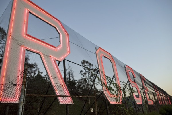 Photo: The Rose Hills cemetery's famed neon sign, just lit up as the sun starts to set. Credit: Maya Sugarman/KPCC