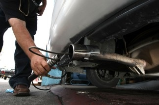 A mechanic inserts a probe into the tailpipe of a car while performing an emissions test in San Francisco, California. The Obama administration is expected to further regulate carbon emissions soon.