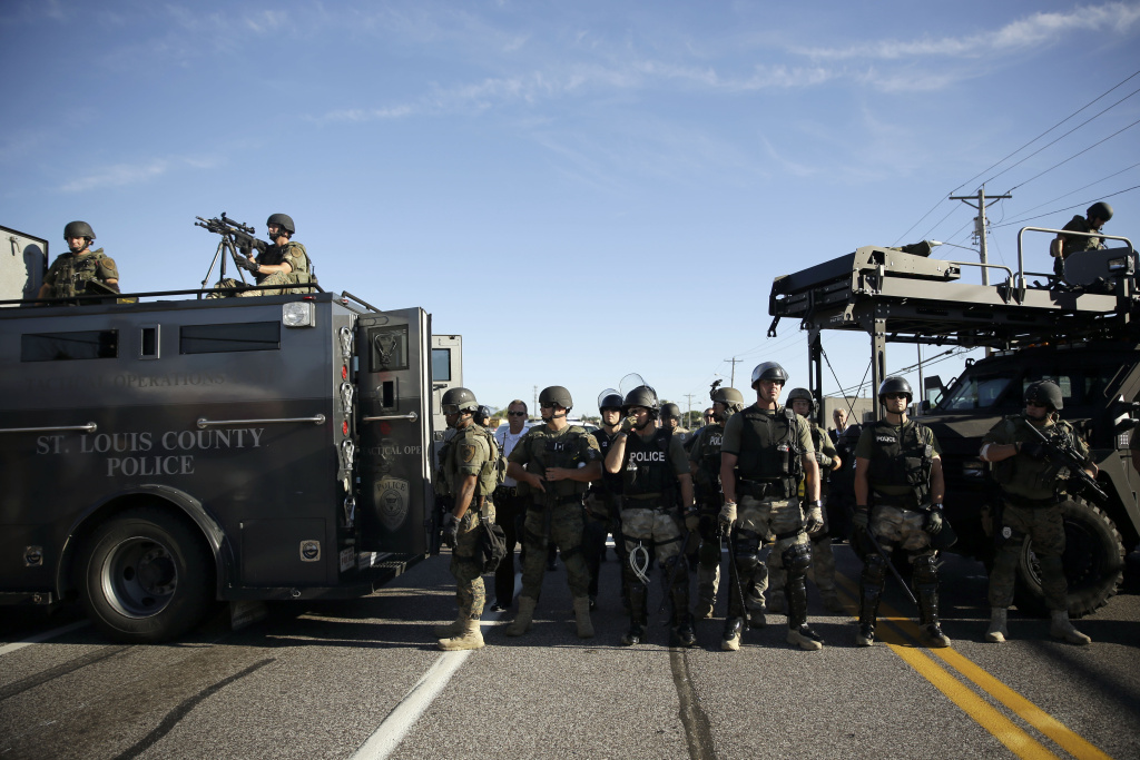 This file photo shows police in riot gear watch protesters in Ferguson, Mo. on Wednesday, Aug. 13, 2014. Images of the police response to protests sparked after the fatal police shooting of teen Michael Brown have prompted legislators to draft legislation that would curb a military surplus program that supplies local law enforcement agencies with machine guns and other equipment.