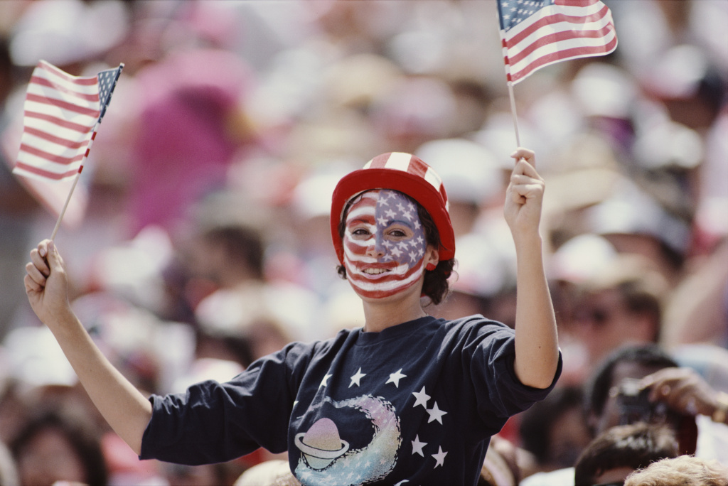 File: A fan waves two United States flags during the opening ceremony for the XXIII Olympic Games on July 28, 1984 at the Los Angeles Memorial Coliseum in Los Angeles, California.