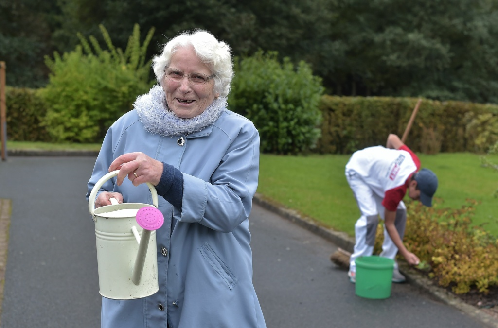 A woman with Alzheimer's disease holds a watering can in the garden of a retirement home on October 18, 2016 in Saint Quirin, France.