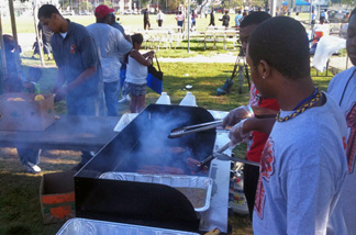 Crew members from the Summer Night Lights program serve burgers and hot dogs