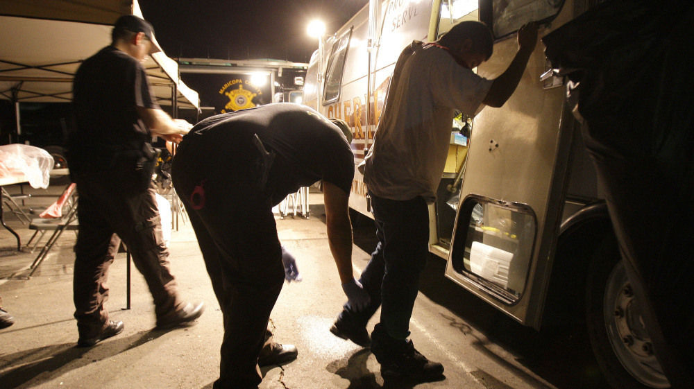 Maricopa County sheriff's deputies check the shoes of a suspect arrested during a crime suppression sweep in Phoenix in 2010.