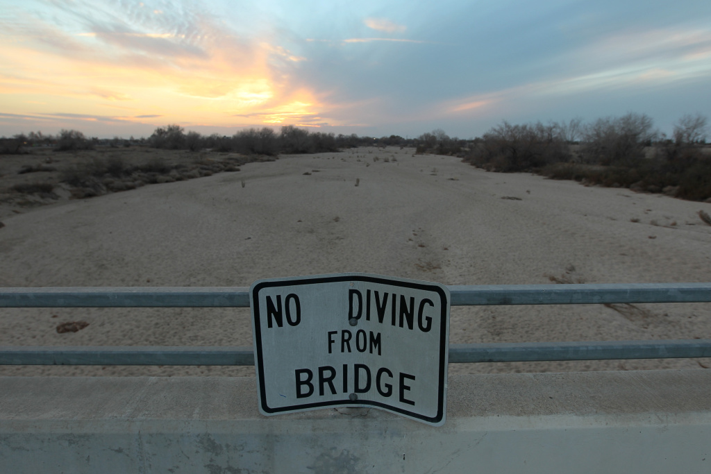 A sign from wetter times warns people not to dive from a bridge over the Kern River, which has been dried up by water diversion projects and little rain, on February 4, 2014 in Bakersfield, California.  (Photo by David McNew/Getty Images)