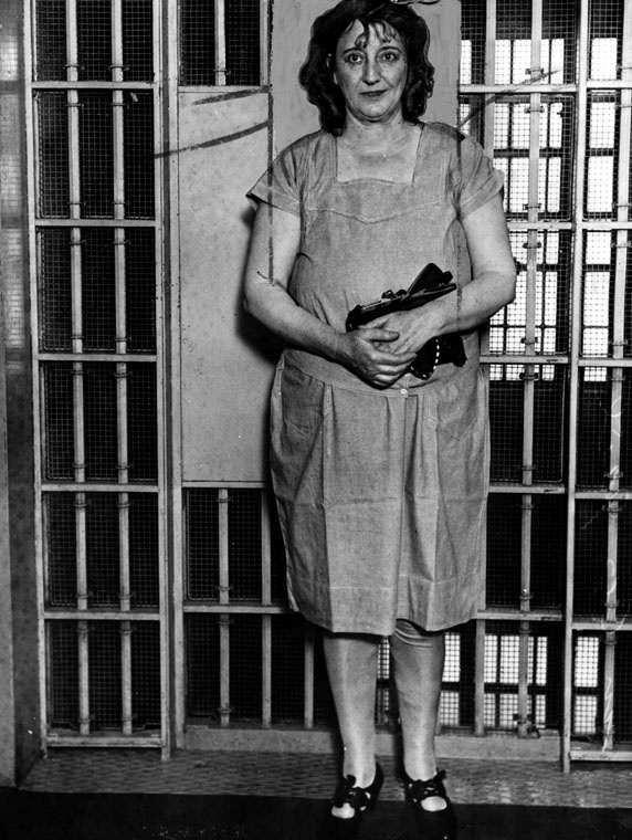 Mrs. Walburga Oesterreich standing in front of a jail cell.