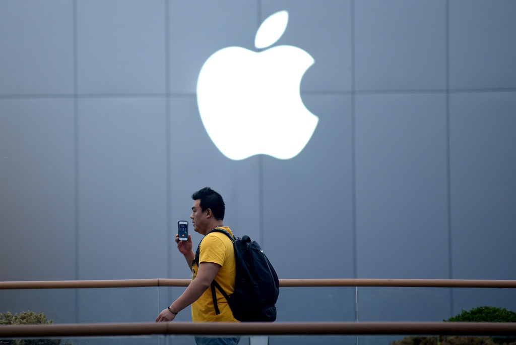 File photo: A man talks on his phone in front of the Apple logo.