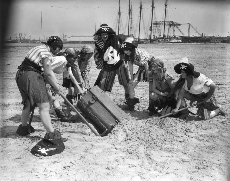 Women pirates in costume pull a buried treasure chest from a hole they dug on the beach at the 1928 Pacific Southwest Exposition in Long Beach.