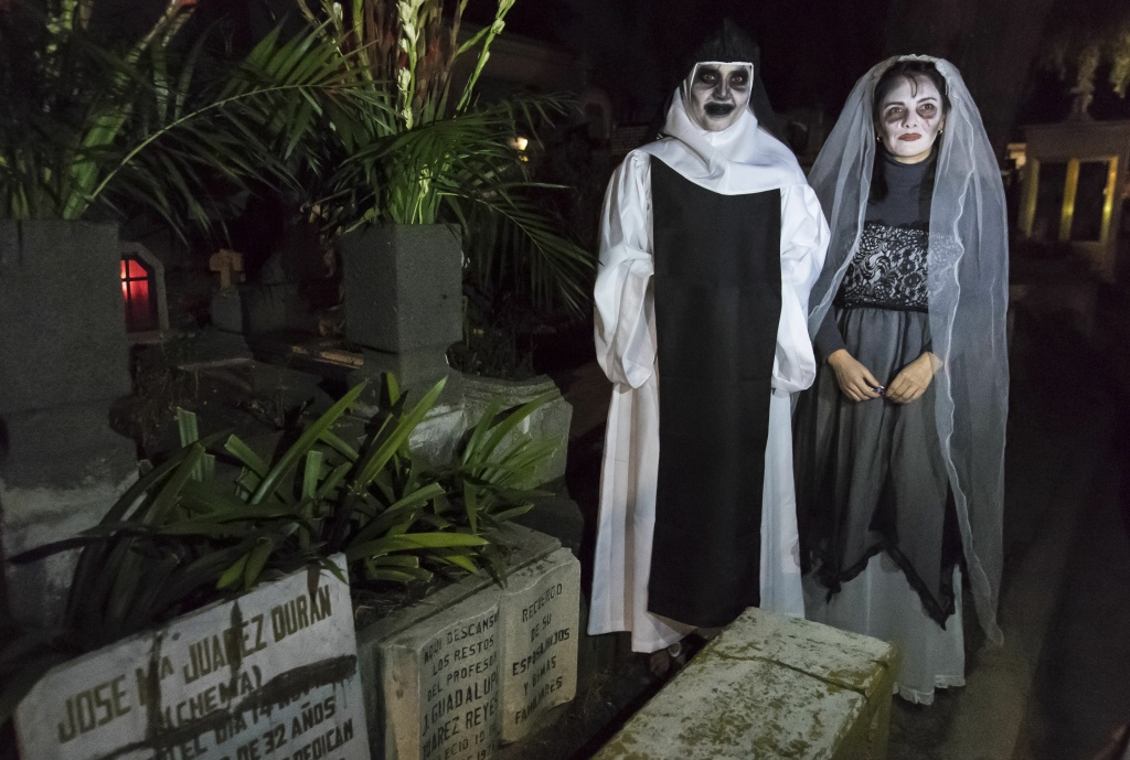 Tonatzin Cortes and Iyelitzin Cortes wear costumes during a visit to their relative's graves at the San Francisco Cemetery in Mexico City on November 1, 2016.