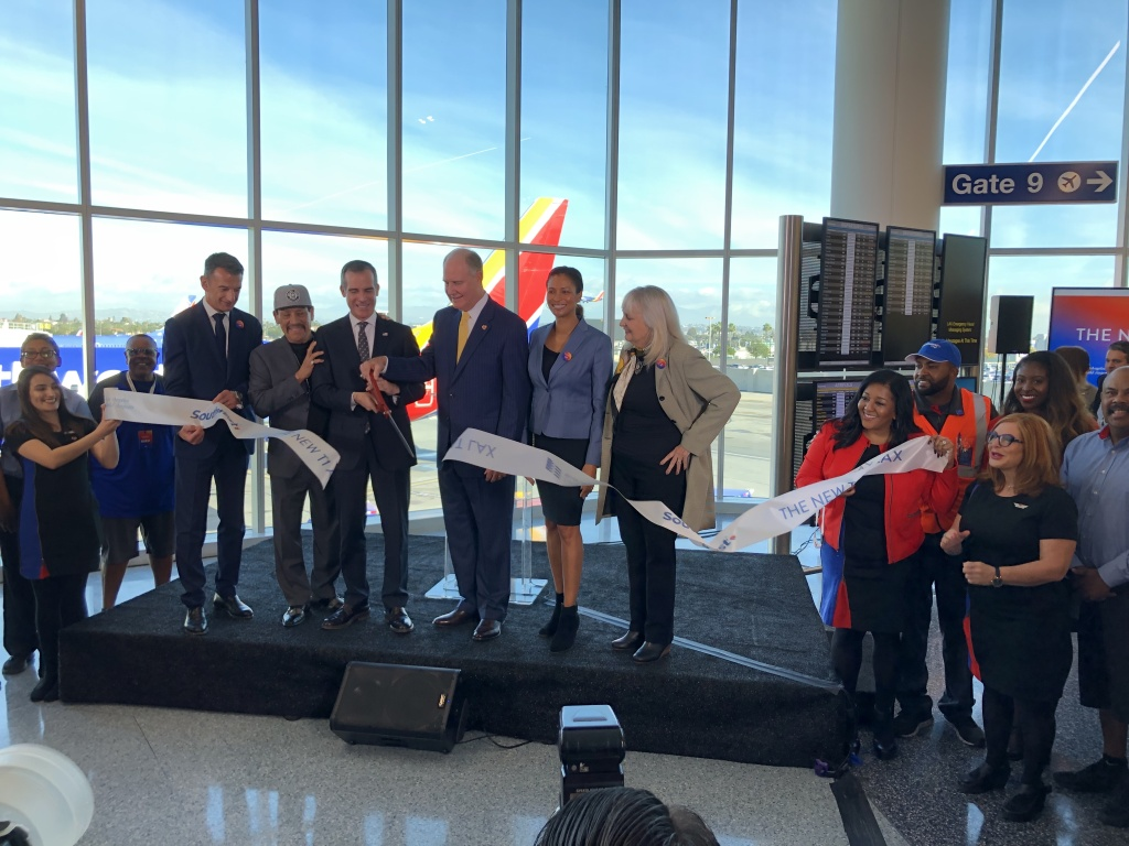 Officials and air travel representatives cut the ribbon on LAX's newly-renovated Terminal 1.