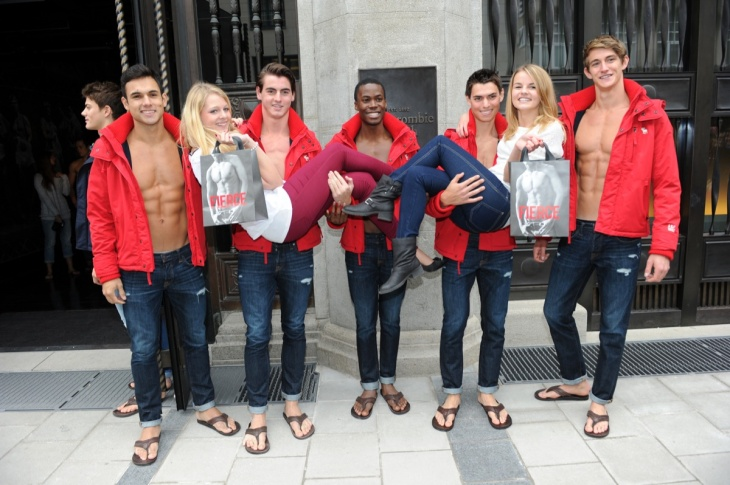 Young women pose for photographs with male models outside the Abercrombie & Fitch flagship clothing store during the opening of Abercrombie & Fitch Munich flagship store on Oct. 25, 2012 in Munich, Germany.