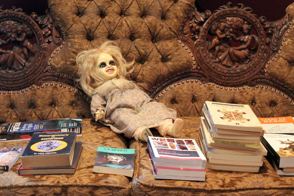 A couch piled with books and a demonic doll.