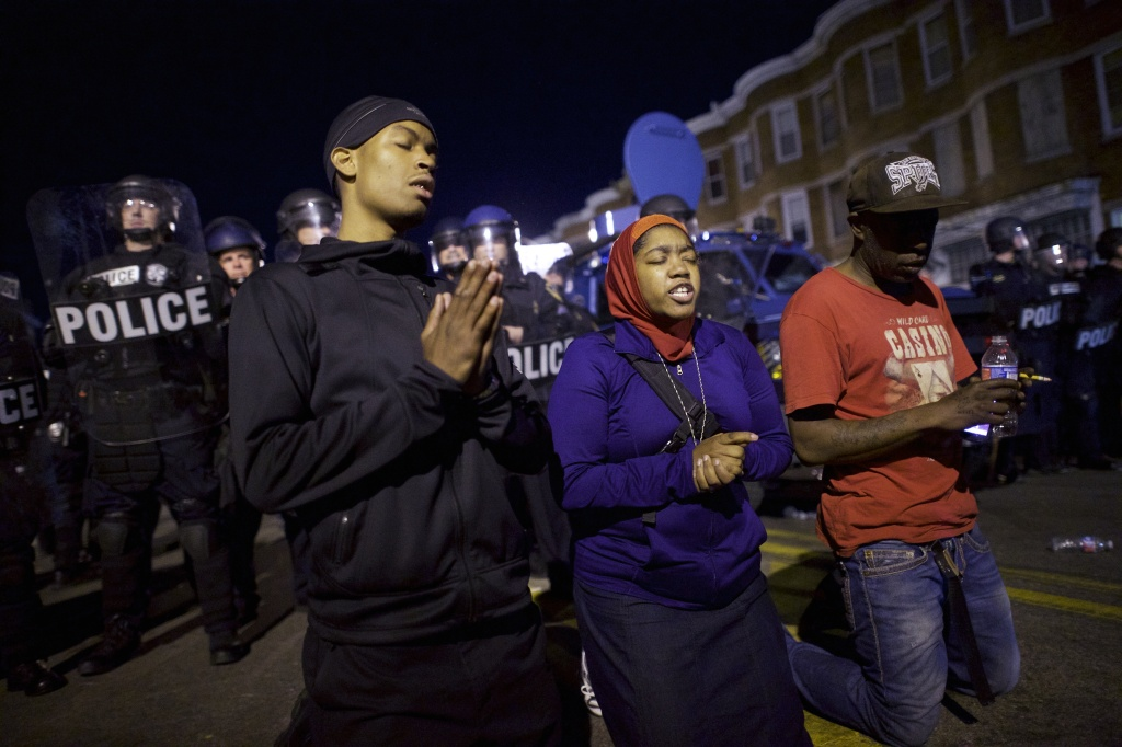 Protestors say the Lord's Prayer beside riot police the night after citywide riots over the death of Freddie Gray on April 28, 2015 in Baltimore, Maryland.