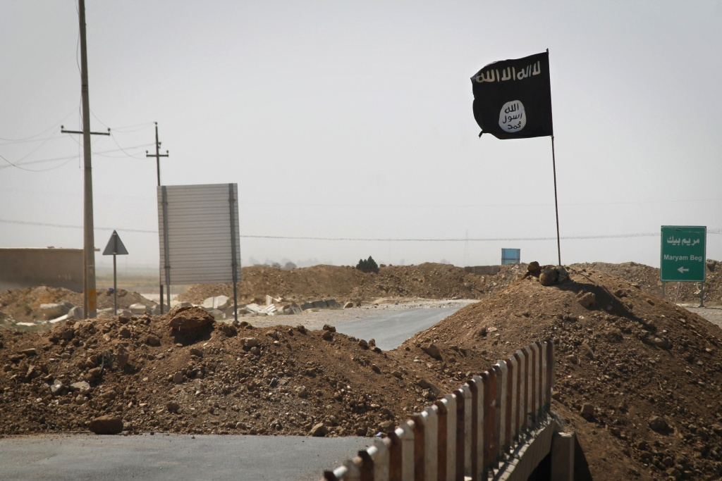 A flag of the Islamic State (IS) is seen on the other side of a bridge at the frontline of fighting between Kurdish Peshmerga fighters and Islamist militants in Rashad.