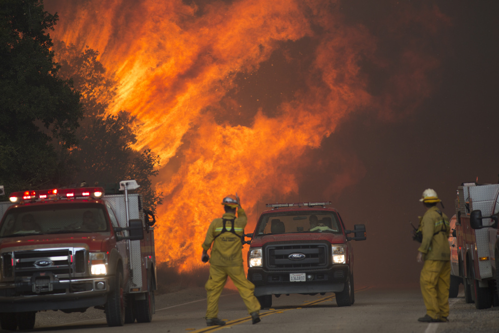 SANTA CLARITA, CA - JULY 24: Firefighters are forced to retreat as flame close in on them in Placerita Canyon at the Sand Fire on July 24, 2016 in Santa Clarita, California. Triple-digit temperatures and dry conditions are fueling the wildfire, which has burned across at least 22,000 acres so far and is only 10% contained. (Photo by David McNew/Getty Images)