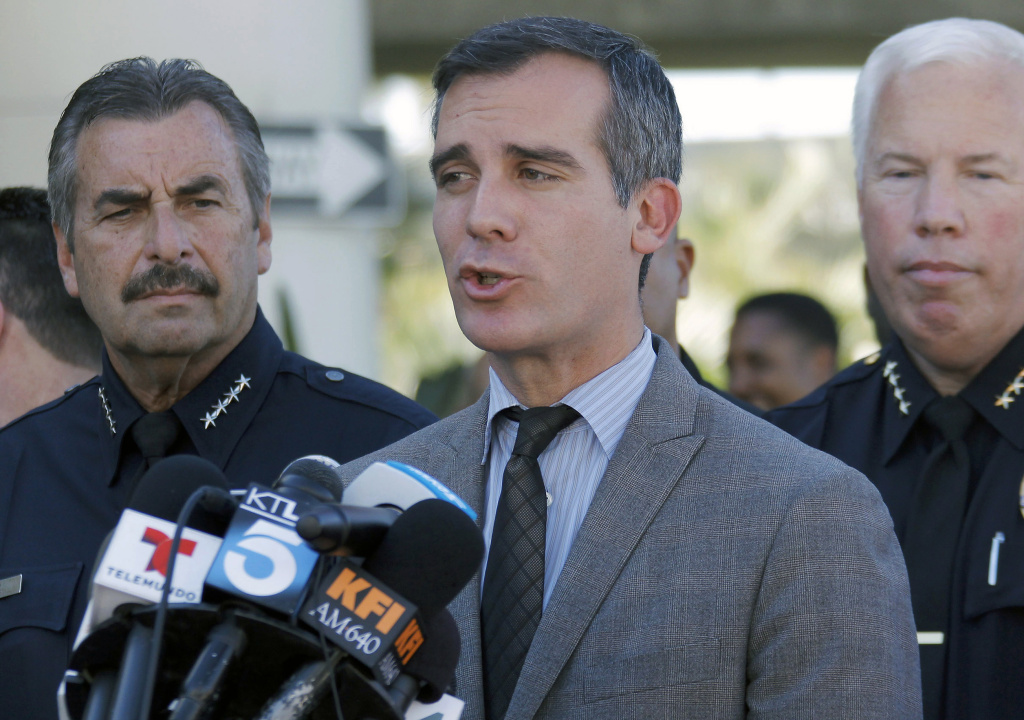 File photo: Los Angeles Police Chief Charlie Beck, left, joins Los Angeles Mayor Eric Garcetti, center, during a news conference at Los Angeles International Airport on Friday Nov. 1, 2013. The union representing LAPD officers on Saturday said its members have rejected a proposed contract with the city. Garcetti said he was disappointed but remained committed to reaching a